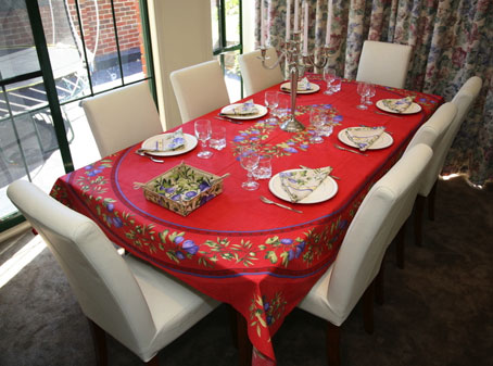 8 seater French provincial tablecloth with oval designs of figs on a red background.